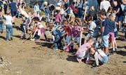 Beim Spatenstich packen die Kinder tatkräftig mit an. Bild: Gianni Amstutz