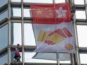 Der Extremkletterer Alain Robert rollte am Freitag in Hongkong an einem Wolkenkratzer ein «Friedensbanner» aus. (Bild: KEYSTONE/AP/VINCENT THIAN)
