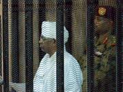 Der in eine weisse sudanesische Robe gekleidete angeklagte frühere Machthaber Sudans, Omar al-Baschir, verfolgt den Prozess aus einem Gitterkäfig im Gerichtssaal. (Bild: KEYSTONE/EPA/STRINGER)