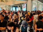 Ins Freie gerannt: Menschen stehen ausserhalb einer Shopping Mall in Jakarta. (Bild: KEYSTONE/AP/DITA ALANGKARA)