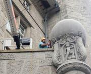 Ein Mitarbeiter einer Spezialfirma bei der Reinigung der Weltkugel über dem hinteren Eingang der Hauptpost am Bahnhofplatz. (Bild: Reto Voneschen -13. August 2019)