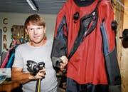 Tauchlehrer Richard Schröter mit einem Trockenanzug, der im kühlen Bodenseewasser mit Vorteil verwendet wird. Die erste Stufe (links) wird an der Pressluftflasche befestigt und muss kaltwassertauglich sein, was heute in der Regel die Norm ist. (Bild: Rudolf Hirtl)