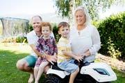 Oscar Adby (4) sitzt auf seinem Spielzeug-Traktor, umgeben von seinen Liebsten: Vater Richard, Zwillingsschwester Elin und Mutter Camilla Adby in ihrem Garten in Wiedlisbach (BE). (Bild: André Albrecht)