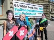 Gegen das Mercosur-Abkommen: Als Simonetta Sommaruga, Guy Parmelin und Jair Bolsonaro Maskierte bei der Petionsübergabe. (Bild: Ben Zumbühl/Campax)