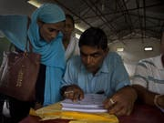 Dorfbewohner von Barburi im indischen Bundesstaat Assam kontrollieren, ob ihre Namen ins Nationale Bürgerregister aufgenommen worden sind. (Bild: Keystone/AP/ANUPAM NATH)