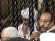 Sudans langjähriger Machthaber Omar al-Baschir (im Bild weiss gekleidet) muss sich wegen der illegalen Beschaffung und Nutzung ausländischer Gelder vor Gericht verantworten. Ein Gericht in der Hauptstadt Khartum klagte den Ex-Staatschef am Samstag formell an. (Bild: KEYSTONE/AP)