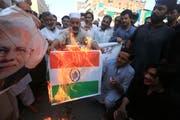 Aufgebrachte Menschen verbrennen die indische Flagge und protestieren dagegen, dass Indien die Autonomie für Kaschmir aufhebt. (Bild: Bilawal Arbab/EPA, 05. August 2019)