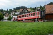 Passanten machen ein letztes Bild vom Bahnwagen, der die Werkstatt in Gais auf der Strasse verlässt. Bild: Karin Erni