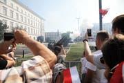 Besucherinnen und Besucher beobachten und filmen die Zeremonie auf dem Pilsudski-Platz. (Bild: EPA)