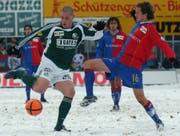 Tanz auf dem schneebedeckten Espenmoos-Rasen: St.Gallens Eric Hassli (links) zieht gegen Basels Patrick Müller ab. (Bild: Keystone)