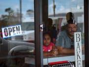 Skeptische Blicke auf die Verwüstung: Ein Mann und ein Mädchen schauen aus einer Bäckerei in Freeport auf den Bahamas. (Bild: KEYSTONE/AP/RAMON ESPINOSA)