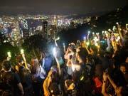 Regierungskritiker in Hongkong bilden am Victoria Peak eine Menschen- und Lichterkette. (Bild: KEYSTONE/EPA/JEROME FAVRE)