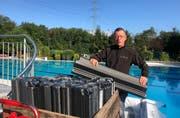 Thomas Kroll bringt die Eisbrecher an: Sie schützen das Schwimmbad im Winter bei Eis und Wetter vor Schäden. (Bild: Jessica Nigg)