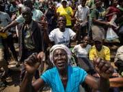 Menschen singen, während sie Schlange stehen, um von Simbabwes Ex-Präsident Robert Mugabe Abschied zu nehmen. Er wurde in einem Stadium in der Hauptstadt Harare aufgebahrt. (Bild: KEYSTONE/AP/BEN CURTIS)