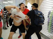 Rangeleien zwischen einem Peking-freundlichen Demonstranten (im roten T-Shirt) und China-kritischen Demonstranten im Einkaufszentrum Amoy Mall. (Bild: KEYSTONE/AP/KIN CHEUNG)