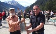 Projektleiter Urs Thali (links) überreicht Bürgerratspräsident Beat Tresch einen Spaten, womit die Rinnen an der neuen Strasse gut geeinigt werden können. Bild: Paul Gwerder (14. September 2019)