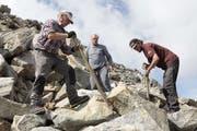 Zivildienster Max Jaquenoud (rechts), Ernst und Ruedi Dubacher arbeiten am Weg zur dreifachen Kontinentalen Wasserscheide im Gotthardgebiet. (Bild: Florian Arnold, 27. August 2019)