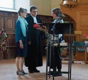 Dekanin Esther Walch Schindler (rechts) segnet den neuen Pfarrer Beat Müller und seine Frau Theresia. Bild: PD