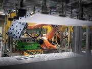 Automatisierte Fertigung von Teilen: Der Schweizer Autozulieferer Autoneum beliefert Hersteller weltweit mit Komponenten für den Schall- und Wärmeschutz in Fahrzeugen. (Bild: KEYSTONE/GAETAN BALLY)