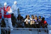 Die italienische Küstenwache evakuiert Migranten, die zuvor wochenlang auf dem Rettungsschiff «Open Arms» ausharren mussten. Italien hatte dem Schiff verboten, in einem italienischen Hafen einzulaufen. (Bild: Keystone, (17. August 2019))