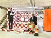 Rot-Weiss geplätteltes Badezimmer im Keller mit Zwillingen und Komplizen, sprich Kunden. (links David Ganz, CEO der Plättli Ganz AG; rechts Guido Koller, Fabrik am Rotbach Immobilien AG) (Bild: PD)
