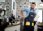 Arkan Nuri schnürt seine Barbier-Schürze in seinem Geschäft in der Zuger Altstadt. (Bild: Stefan Kaiser, Zug, 23. September 2019)