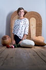 Der Tod muss nicht nur schwarz sein: Angela Villiger mit zwei Holzurnen und einer aus Lehm. (Bild: Maria Schmid, Zug, 25. September 2019)