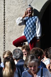 Ein Gaukler steht auf dem Geländer der Zugbrücke und unterhält die Besucher des Erntedankfestes. (Bild: Manuel Nagel)
