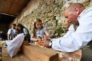 Schreiner Franz Warger (r.) stellt mit den Kindern Arvenkissen her. Die Holzspäne wegzuhobeln ist gar nicht so einfach. (Bild: Manuel Nagel)