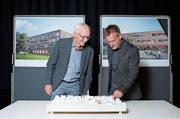 Gemeinderat Beat Iten (links) und Architekt Christophe Egli vor einem Modell des neuen Schulgebäudes und der Umgebung. Im Hintergrund sind die Visualisierungen des Gebäudes von beiden Seiten zu sehen. (Bild: Maria Schmid, Unterägeri, 27. September 2019)