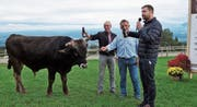 Der Muni von Züchter Walter Rüttimann (Mitte) wird von Spender Kilian Küng (rechts) und Götti Willy Weber auf den Namen Kümu getauft.Bild: Eddy Schambron