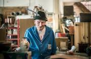 Richard Neururer mit einem Hut und Feder in seinem Reich, das er sich geschaffen hat. (Bild: Andrea Stalder).