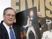 Der Elvis-Fotograf Ed Bonja posiert am 13. Aug. 2007 in Berlin mit einem Foto des «King of Rock 'n' Roll» vor einem Ausstellungsplakat. Im September 2019 ist Bonja im Alter von 74 Jahren gestorben. (Bild: Keystone/AP/MICHAEL SOHN)