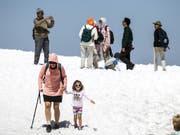 Touristen geniessen die sommerlichen Temperaturen auf dem Titlis im Schnee: Im Juli haben erneut mehr Ausländer hierzulande übernachtet. Besonders die Lust der Amerikaner, die Schweiz zu bereisen, nimmt zu. (Bild: KEYSTONE/ALEXANDRA WEY)