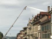 Ein Feuerwehrmann bekämpft von einer Drehleiter aus den Dachstockbrand. (Bild: Kantonspolizei Freiburg)