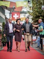 Dieses Trio macht eine gute Figur: Richard Ziegler, Initiant der Modeschau, läuft mit Petra Gimmi und Roland Wyss über den roten Teppich. (Bild: Reto Martin)