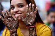 Eine junge indische Frau mit einem kunstvollen Henna-Tattoo. (Bild: Sanjeev Gupta/EPA - 14. August 2019)