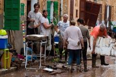 Bewohner putzen ihre Häuser. (Bild: AP Photo/Francisco Ubilla)