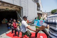 Helfer und Mitarbeiter des Militärs bringen Hilfsgüter an Land. (EPA/MADE NAGI)