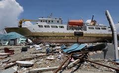 Ein Schiff ist mit dem Tsunami an Land gestrandet. (AP Photo/Tatan Syuflana)