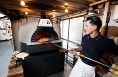 Pizzaiolo Luli Selimi von Woody Pizza schmeisst eine Margaritha in den Ofen.(Bild: Stefan Kaiser (Zug, 23.Oktober 2018))