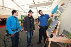 Rainer Henggele mit Sohn Jonas stellen dem Polizisten Marcel Müller am Stand der Zuger Polizei Fragen über den Verkehr. (Bild: Roger Zbinden (Zug, 20. Oktober 2018))