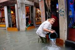Diese Frau schöpft Wasser aus einem überfluteten Laden. (Bild: Andrea Merola/Keystone (29. Oktober 2018))