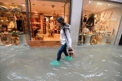 Eine Frau schreitet durch eine überflutete Strasse in Venedig. Gemäss den Behörden stehen 70 Prozent des historischen Zentrums der Stadt unter Wasser. (Bild: Andrea Merola/Keystone (29. Oktober 2019))