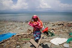 Eine Bewohnerin von Zentral-Sulawesi auf der Suche nach brauchbaren Materialien am Strand. Kasma floh bergaufwärts mit ihren zwei Kindern vor dem Tsunami, der ihr Haus zerstörte. (Bild: EPA/MAST IRHAM)