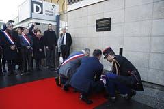 Der französische Premierminister Edouard Philippe (Mitte) und der Bürgermeister des Pariser Vororts Saint-Denis, Laurent Russier (links mit Trikolore-Band) legen vor der Gedenktafel beim Stade de France Blumen nieder. (Bild: Yoan Valat/EPA (Paris, 13. November 2018))