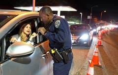 Ein California Highway Patrol Officer kontrolliert, ob die Dame, die nach Malibu zurück will, auch tatsächlich dort Wohnsitz hat. Der Evakuationsbefehl wurde für den Ostteil der Stadt aufgehoben. (Bild: AP Photo/Reed Saxon/13. November 2018)