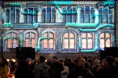 Besucher verfolgen die Lichtprojektionen anlässlich des Weihnachtsfestivals im Landesmuseum in Zürich. (KEYSTONE/Ennio Leanza, 15. November 2018)