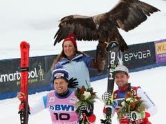 Sieger Beat Feuz (rechts) und der zweitklassierte Teamkollege Mauro Caviezel posieren bei der Siegerehrung mit einem Adler (Bild: KEYSTONE/EPA/JOHN G. MABANGLO)