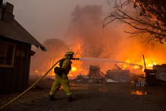 Ein Mitarbeiter der Feuerwehr bekämpft die Flammen. (EPA/PETER DASILVA)